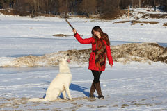 Woman playing with white dog in winter Stock Photo