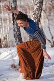 Woman playing in winter snow. Attractive young woman playing in winter snow with wood in background Royalty Free Stock Photography