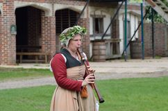 Woman  playing wooden medieval flute in reenactment Stock Photo