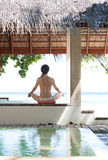 Woman playing yoga in maldives beach resort. Woman playing yoga at thatched pavilion in maldives beach resort Royalty Free Stock Photo