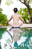 Woman playing yoga beside the swimming pool Royalty Free Stock Images