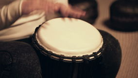 Woman plays beat on djembe, African drum stock footage