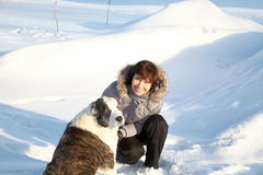 Woman plays with a dog in the winter  day Royalty Free Stock Photos