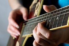 Woman plays an electric guitar Royalty Free Stock Photos