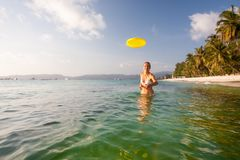 Woman plays frisbee in the water of beautiful ocean Royalty Free Stock Images