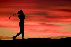 A woman plays golf against a brilliant sunset