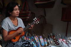 Woman plays guitar at the market Stock Images