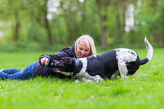 Woman plays with her dog outdoors Royalty Free Stock Images