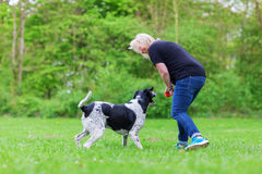Woman plays with her dog outdoors Royalty Free Stock Photography