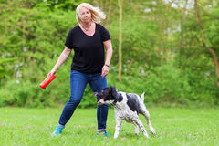 Woman plays with her dog outdoors Stock Images
