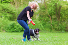 Woman plays with her dog outdoors Royalty Free Stock Image