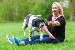 Woman plays with her dog outdoors Stock Photography