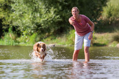 Woman plays with her dog in the water Stock Photos