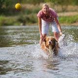 Woman plays with her dog in the water Royalty Free Stock Photos