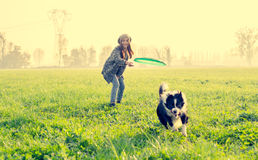 Woman plays with her dog. Young beautiful girl throwing fresbee to her dog in a park at sunset - Asian woman playing with her dog stock image