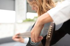 Woman plays her left-handed guitar at home after work in the office Stock Photo