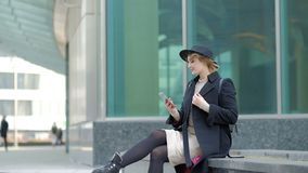 Woman plays with modern black hat moving wide-brimmed chapeau at black coat bottom in street slow motion low angle shot stock video