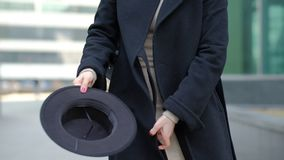 Woman plays with modern black hat moving wide-brimmed chapeau at black coat bottom in street slow motion low angle shot. Woman plays with modern black hat stock video footage
