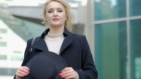 Woman plays with modern black hat moving wide-brimmed chapeau at black coat bottom in street slow motion low angle shot.  stock video footage
