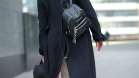 Woman plays with modern black hat moving wide-brimmed chapeau at black coat bottom in street slow motion low angle shot. Woman plays with modern black hat stock video