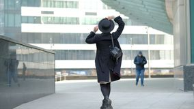 Woman plays with modern black hat moving wide-brimmed chapeau at black coat bottom in street slow motion low angle shot. Woman plays with modern black hat stock footage