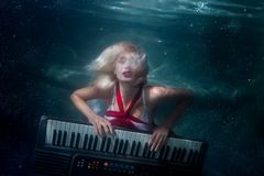 Woman plays music diving under the water. Stock Images
