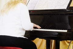 Woman plays the piano Stock Image