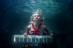 Woman plays the piano underwater. Woman plays the piano under water, she is a mermaid Royalty Free Stock Image
