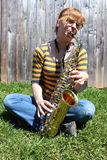 Woman plays saxaphone outdoors. Young woman is playing a shiny saxaphone sitting outdoors with green grass and blue sky (focus on saxaphone and fingers Stock Photography