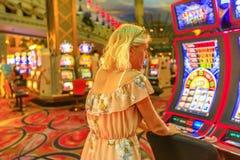 Woman plays slot machines stock image