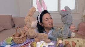 Woman plays with toy bunnies. In room