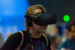 A woman plays a video game using virtual reality glasses Stock Image