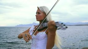 Woman Plays The Violin. Beautiful violinist clad in a beautiful white dress playing the violin. Against the backdrop of a beautiful sky stock video footage