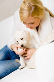 Woman plays with white puppy on the sofa Royalty Free Stock Image