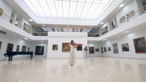 Woman plays wooden violin in a big room in museum. 4K stock footage