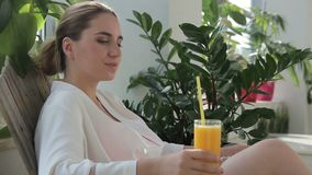 Woman with pleasure drinks freshly squeezed juice, relaxes on deckchair. Among green plants female visitor of spa salon rests after procedures and swallows an stock video footage