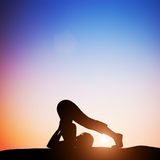 Woman in plow yoga pose meditating at sunset. Zen Stock Photo