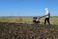 Woman plows the land. With a motor-block Royalty Free Stock Image