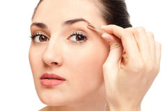 Woman plucking eyebrow tweezers Royalty Free Stock Images