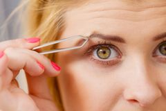 Woman tweezing eyebrows depilating with tweezers. Woman plucking eyebrows depilating with tweezers closeup part of face. Girl tweezing removing her facial hairs Royalty Free Stock Images