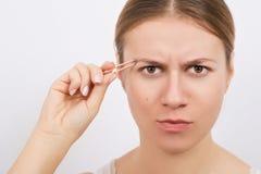Woman plucking eyebrows with tweezers over grey background. Woman plucking eyebrows with tweezers over the grey background Stock Photography