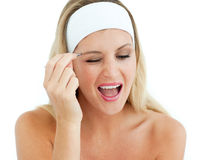 Woman plucking her eyebrows Stock Photos