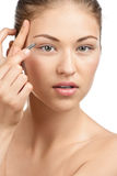 Woman plucking her eyebrows Stock Photography
