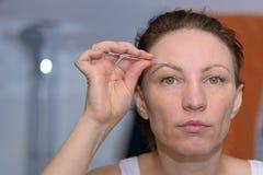 Woman plucking her eyebrows with tweezers. Woman plucking her eyebrows with a pair of small handheld metal tweezers in a beauty concept Royalty Free Stock Image