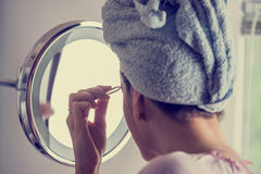 Woman plucking her eyebrows Royalty Free Stock Photos