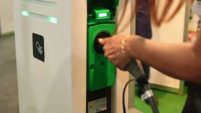 Woman plugging electric car in socket at comfortable public charging station