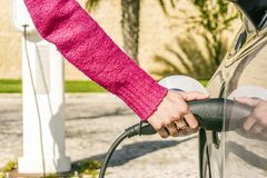 Woman plugs electric car to charging station. In warm climate Stock Photos