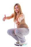 Woman plus size on scale celebrating weightloss thumb up isolated Royalty Free Stock Image