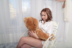 Woman with a plush bear sitting on a chair near the window Royalty Free Stock Photos