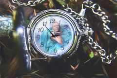 Woman in pocket watch. A composite image of a woman inside a silver pocket watch stock images